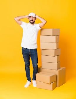孤立した黄色の上のボックスの間で配達人のフルレングスのショットはイライラし、頭に手を取ります