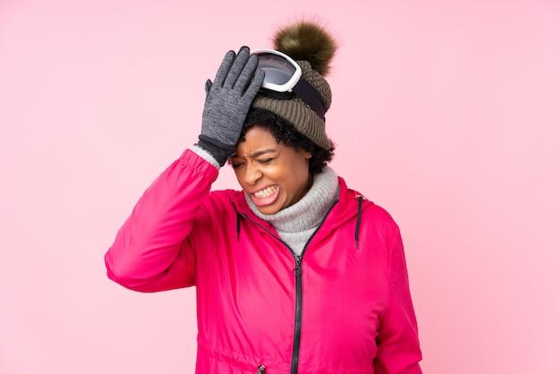 Афро-американских женщина с снежные очки над розовой стеной