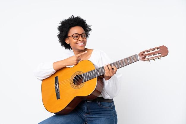 Афро-американских женщина с гитарой на белой стене