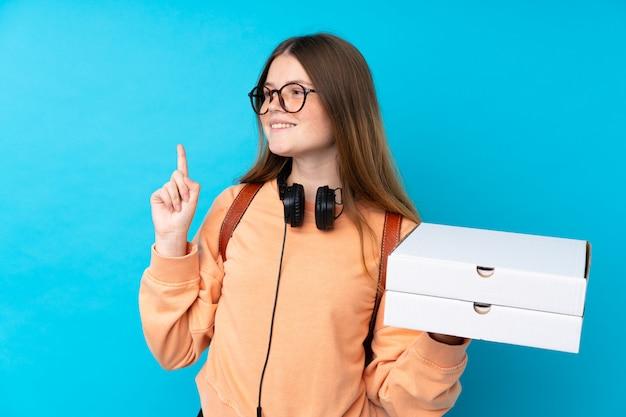 Девушка-подросток держит пиццу над синей стеной