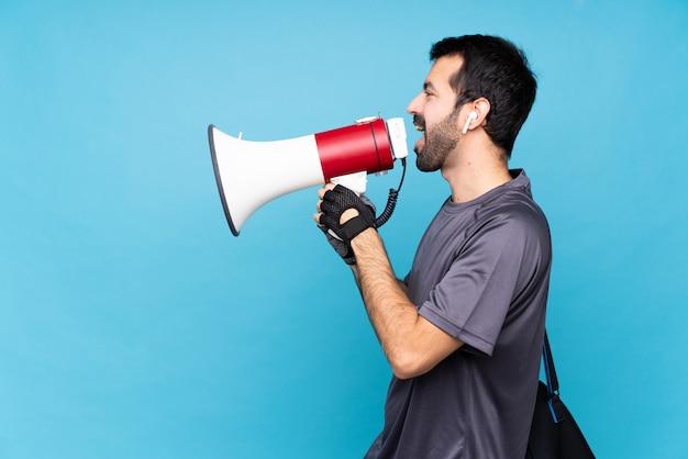 Молодой спортивный человек с бородой над изолированной синей кричать через мегафон
