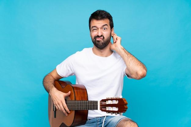 疑問を持つ分離された青の上のギターを持つ若い男