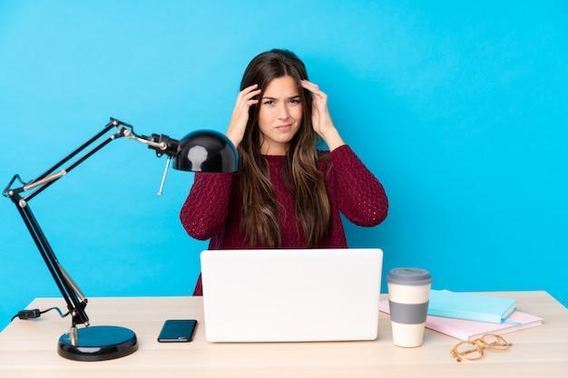 Девушка студента подростка в рабочем месте над голубой стеной