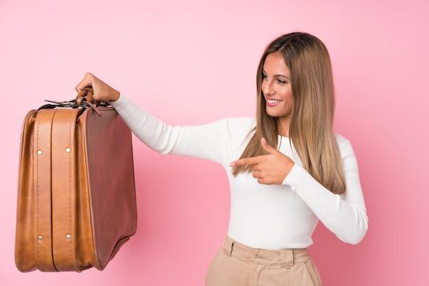Молодая белокурая женщина держа винтажный портфель