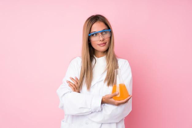 科学的なテストチューブと横向きの若いブロンドの女性