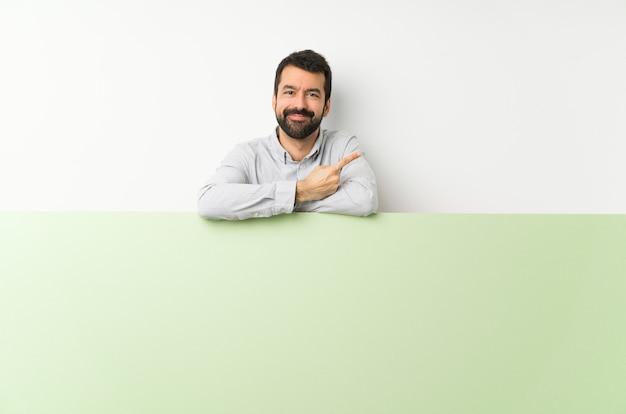 製品を提示する側を指している大きな緑の空のプラカードを保持しているひげの若いハンサムな男