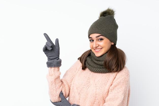 側に指を指している冬の帽子を持つ若い女性