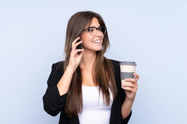 若いブラジルのビジネスの女性がコーヒーを奪うために保持し、携帯電話に話して