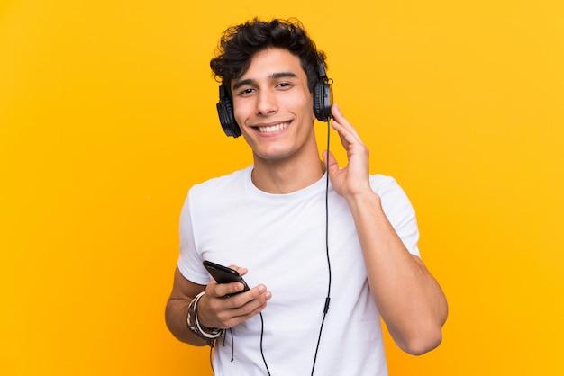 Музыка молодого аргентинского человека слушая с чернью над изолированной желтой стеной
