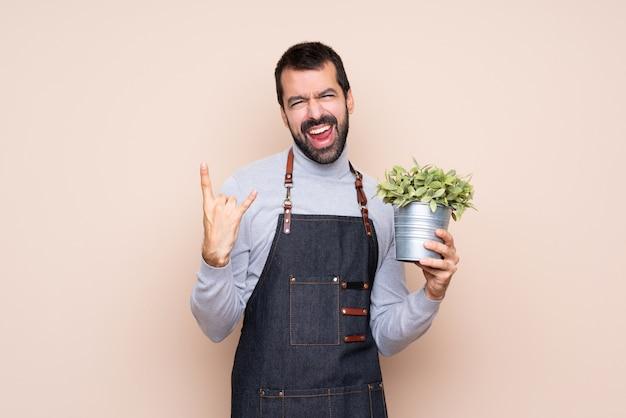 ロックジェスチャーを作る分離で植物を抱きかかえた