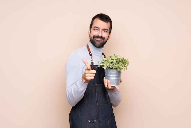 前方を指すと笑みを浮かべて上に植物を保持している男