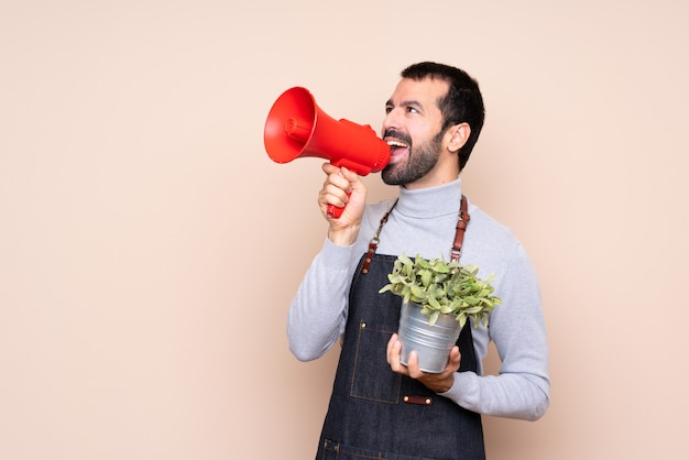 Мужчина держит растение над изолированным криком через мегафон