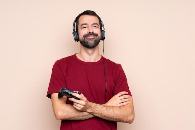 Человек играет с контроллером видеоигры над изолированной стеной, скрестив руки в переднем положении