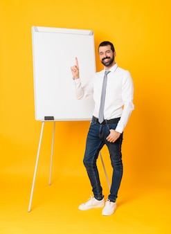 分離された黄色の表示と最高の兆候で指を持ち上げる上ホワイトボードにプレゼンテーションを行う実業家の全身ショット