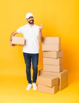 お金のジェスチャーを作る分離された黄色の上のボックスの中で配達人の全身ショット