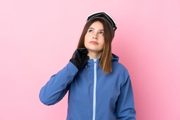 Молодая девушка в зимней шапке над розовой стеной