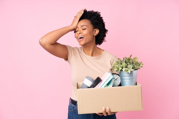 Молодая женщина с коробкой вещей на изолированной стене