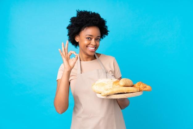Молодая женщина пекарь над синей стеной