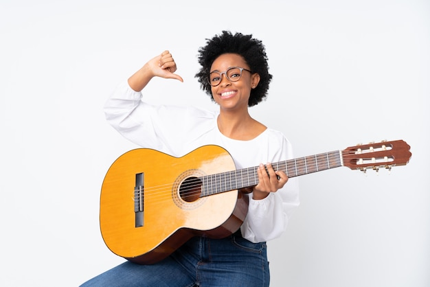Молодая женщина с гитарой на изолированной стене