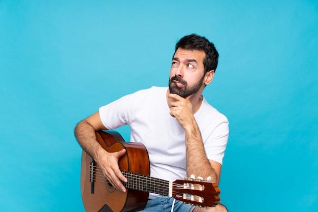 混乱の表情と青の上のギターを持つ若い男