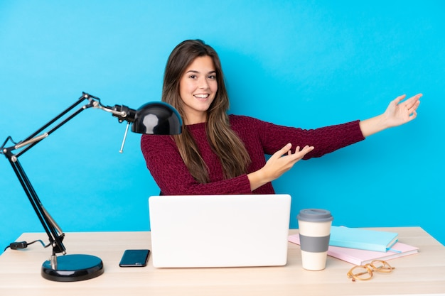 Молодая девушка студента на рабочем месте над голубой стеной