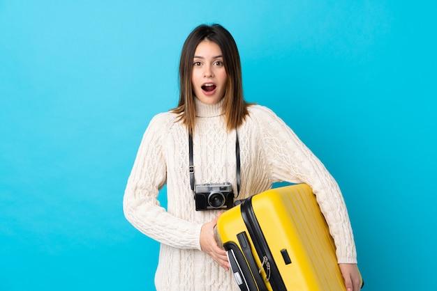 青い壁の上のスーツケースを持つ若い旅行者の女の子