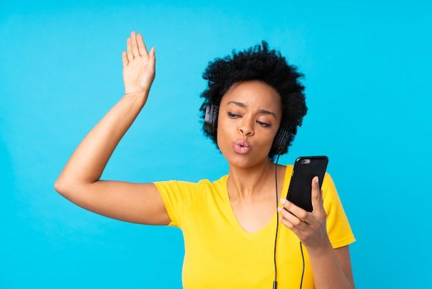 孤立した青い壁を越えて携帯電話で音楽を聴く若いアフリカ系アメリカ人女性