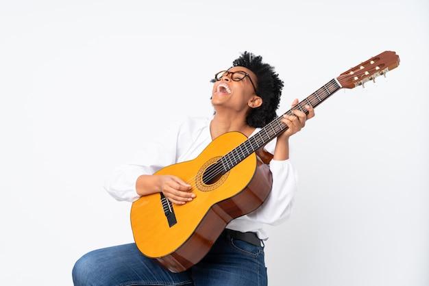 Афро-американская женщина с гитарой над изолированной