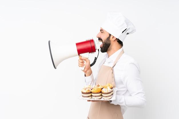 Молодой человек, держащий торт сдобы над изолированным белым криком через мегафон