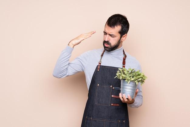 疲れや病気の表情で植物を抱きかかえた
