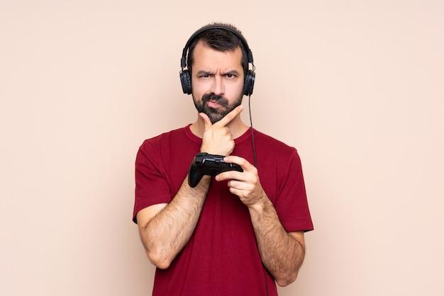 孤立した壁の思考上のビデオゲームコントローラーで遊ぶ男