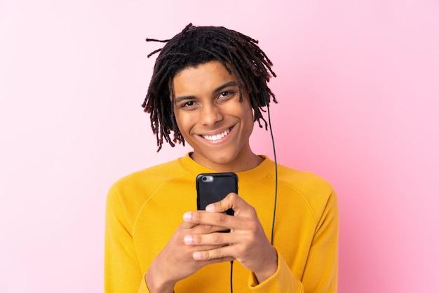 Молодой афроамериканец человек слушает музыку над розовой стеной