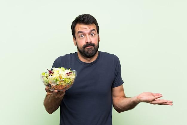 Молодой красавец с салатом на зеленой стене, сомневаясь, поднимая руки