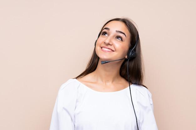 Молодая телемаркетер женщина смотрит вверх во время улыбки