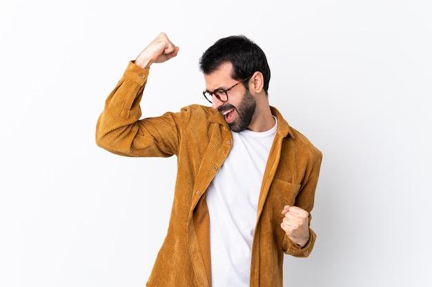 勝利を祝う孤立した白い壁にコーデュロイジャケットを着てひげと白人のハンサムな男