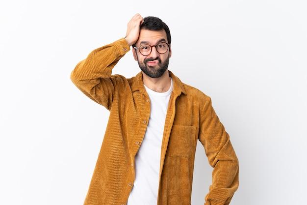 欲求不満の表現と理解していない孤立した白い壁にコーデュロイのジャケットを着てひげを持つ白人のハンサムな男
