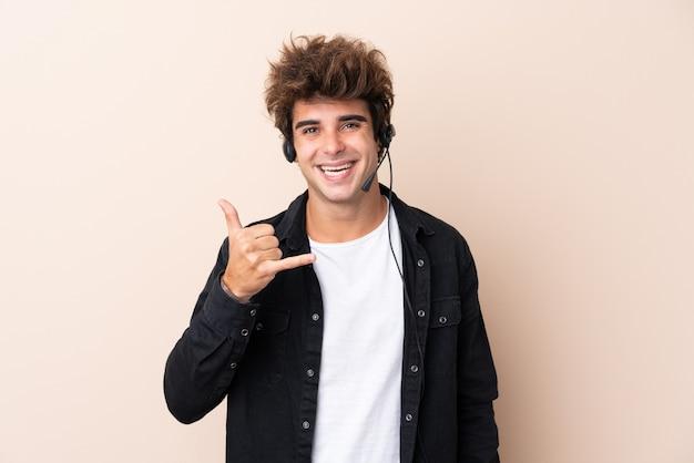電話ジェスチャーを作る分離壁を越えてヘッドセットを扱うテレマーケティング男