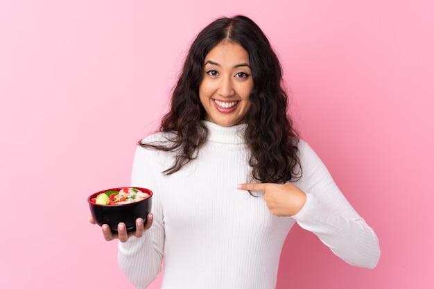 Женщина смешанной расы держит миску с лапшой на изолированной розовой стене с удивленным выражением лица