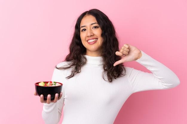 分離されたピンクの壁に麺の完全なボウルを保持している混血の女性誇りと自己満足