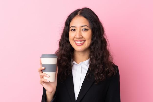 孤立したピンクの壁を奪うためにコーヒーを保持している混血ビジネス女性