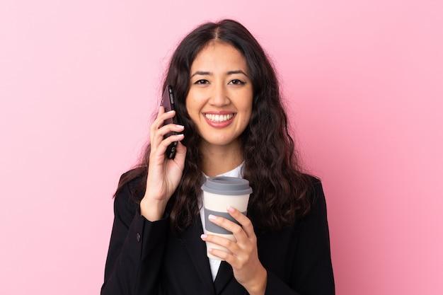 混血ビジネス女性を奪うコーヒーを保持し、分離のピンクの壁を越えて携帯電話に話して