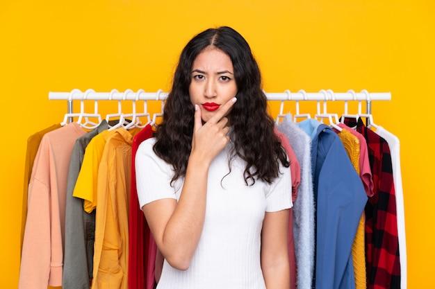 アイデアを考えて衣料品店で混血の女性