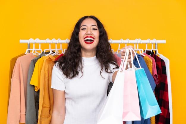 衣料品店で買い物袋を持つ混血の女性