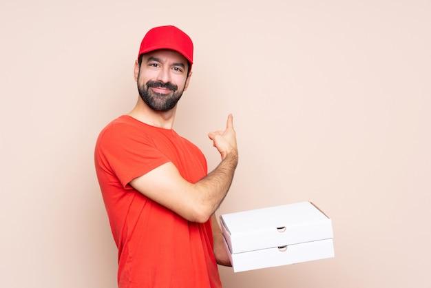 若い男が孤立した壁を越えてピザをかざす