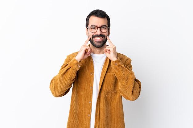 幸せで楽しい表情で笑みを浮かべて白でコーデュロイジャケットを着てひげと白人のハンサムな男