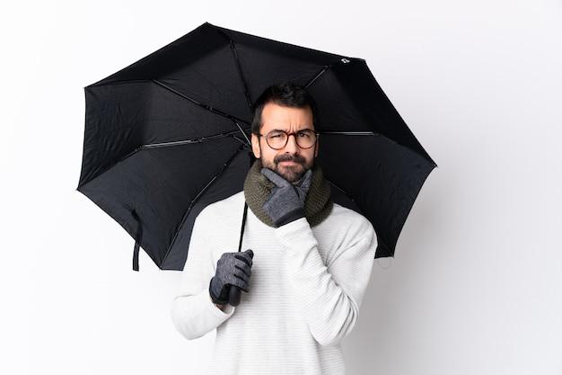 白い壁の思考に傘を保持しているひげの白人のハンサムな男