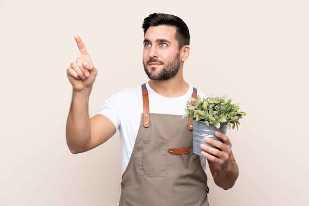透明なスクリーンに触れる上植物を保持している庭師の男