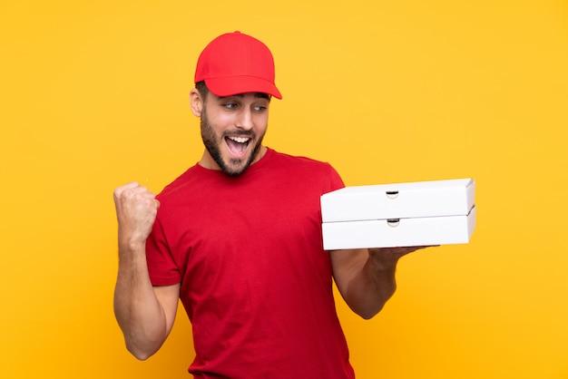 Доставщик пиццы с униформой работы, собирая коробки для пиццы на изолированном желтом праздновании победы