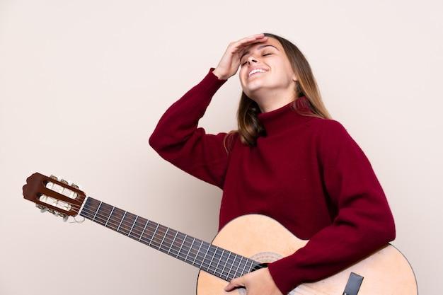 ギターを持つティーンエイジャーの女の子は何かを実現し、解決策を意図しています