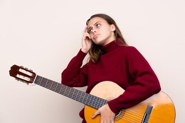疑問を持つギターと混乱の表情とティーンエイジャーの女の子